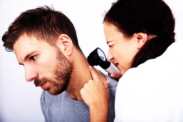 Skin cancer check on a man by general practitioner in GPs on Curzon