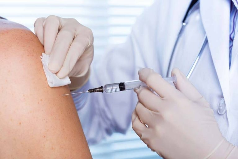 Needle injected on arm for travel vaccination services at GPs on Curzon.