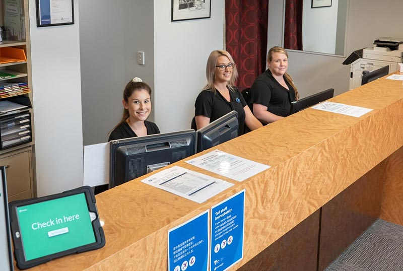 Reception desk at GPs on Curzon showing receptionist at work, doctors in Toowoomba