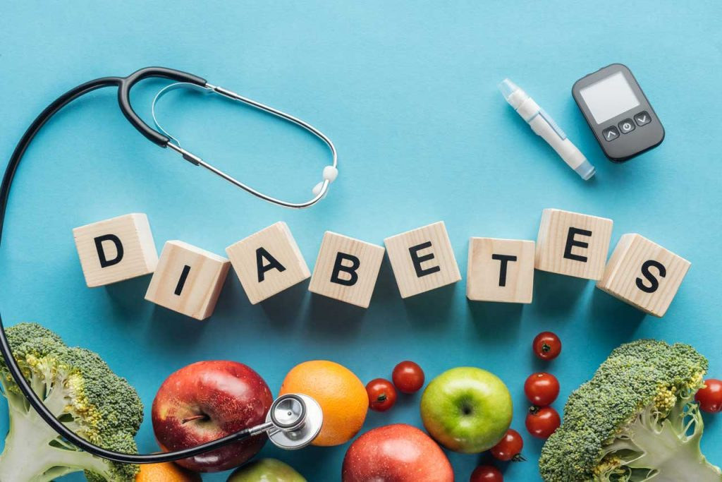 Diabetes lettering surrounded by items that help screen and manage diabetes, including glucose test, healthy fruits and vegetables and a doctors stethoscope as a symbol of professional medical treatment